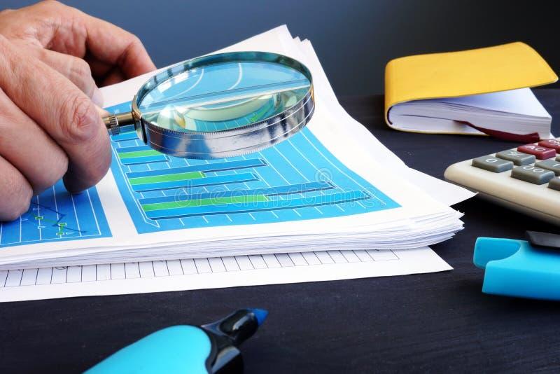 L'uomo sta tenendo la lente d'ingrandimento sopra i documenti di affari con le statistiche finanziarie verifica immagini stock