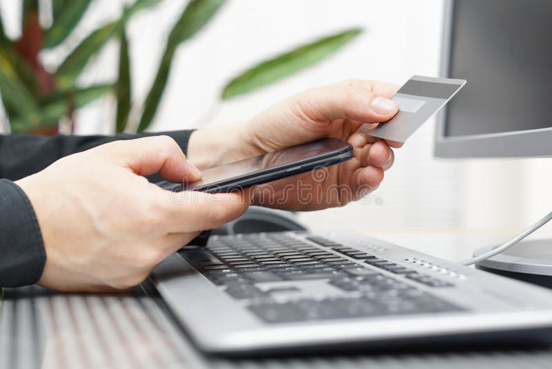 L'uomo sta utilizzando la carta di credito ed il telefono cellulare per sulla linea pagamento immagini stock libere da diritti