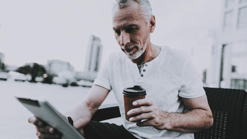 L'uomo sta utilizzando un PC della compressa e sta bevendo un caffè fotografia stock libera da diritti