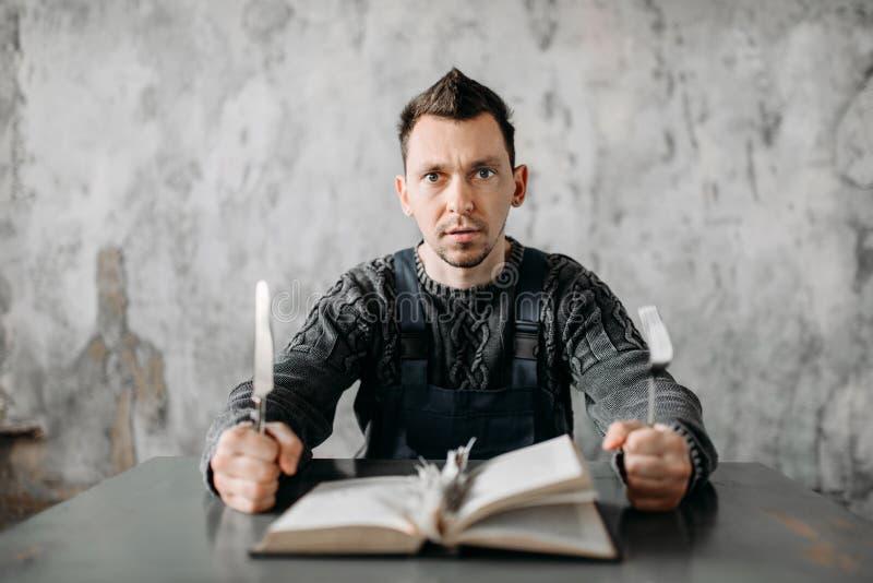 L'uomo strano sconosciuto mangia gli strati dal libro fotografie stock libere da diritti