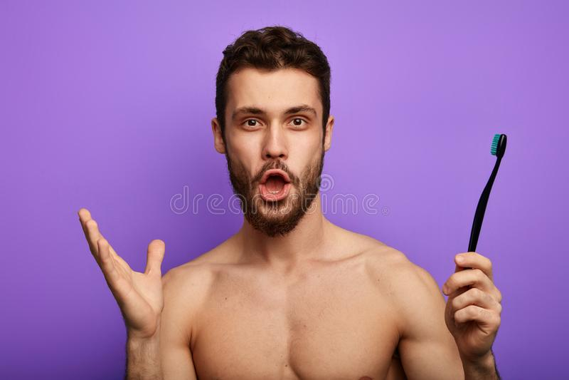 L'uomo stupito con la bocca ampiamente aperta, sguardi fissi alla macchina fotografica, tiene lo spazzolino da denti a disposizio fotografie stock