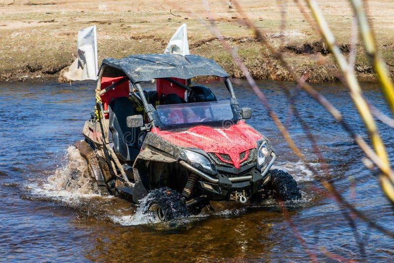 L'uomo sul ATV guida sul fiume con acqua di spruzzatura immagine stock