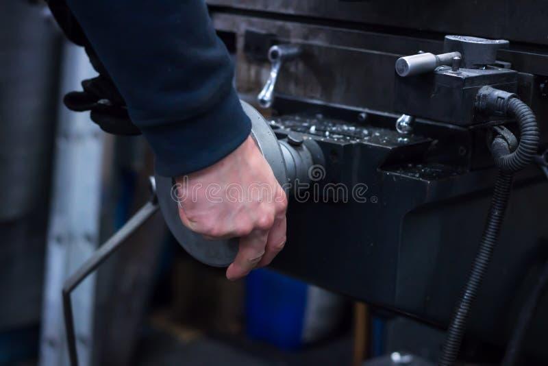L'uomo sulla macchina elabora il dettaglio del metallo fotografie stock libere da diritti
