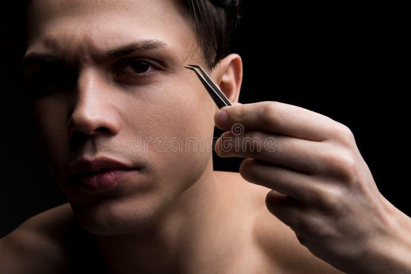 L'uomo sveglio giovanile sta occupandosi del suo aspetto immagine stock