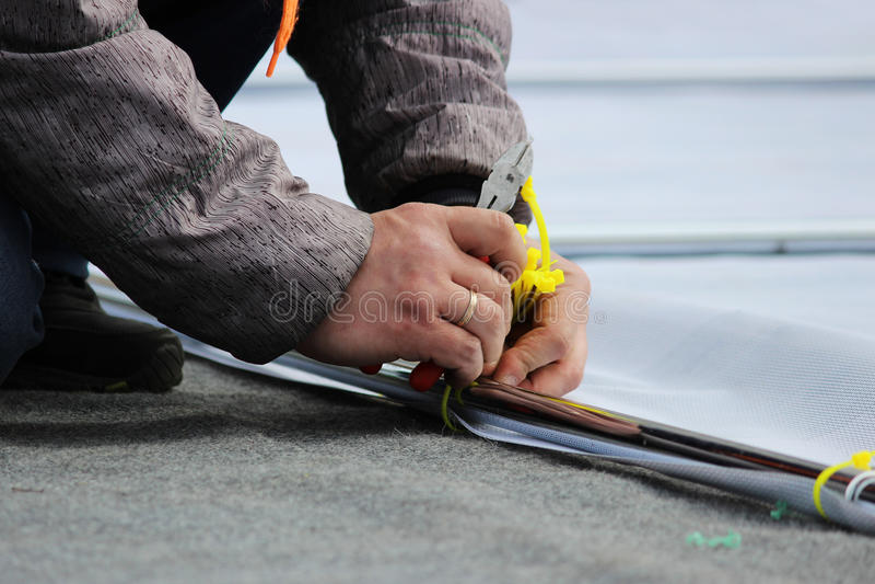 L'uomo taglia i legami di plastica dei morsetti con le pinze dei tagliafili durante lo smantellamento della fase dopo il holi fotografia stock libera da diritti