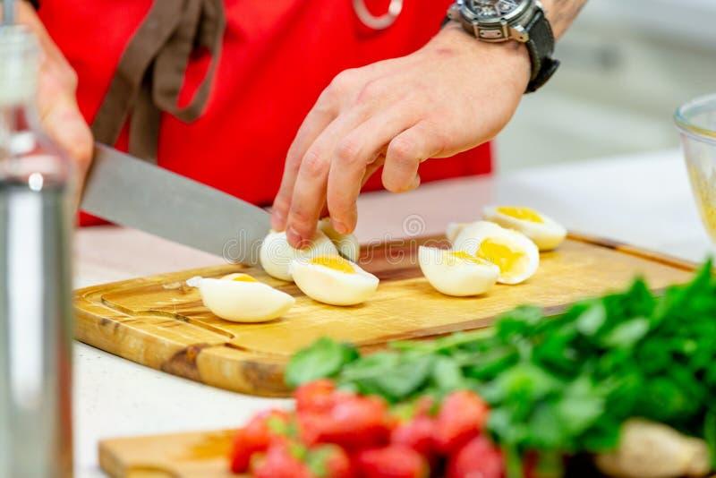 L'uomo taglia le uova di quaglia bollite sul primo piano di legno del tagliere Ricetta graduale del piatto casalingo fotografia stock