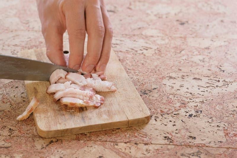 L'uomo taglia un bacon del petto della carne di maiale sui piccoli pezzi su un bordo di legno mano del primo piano fotografia stock