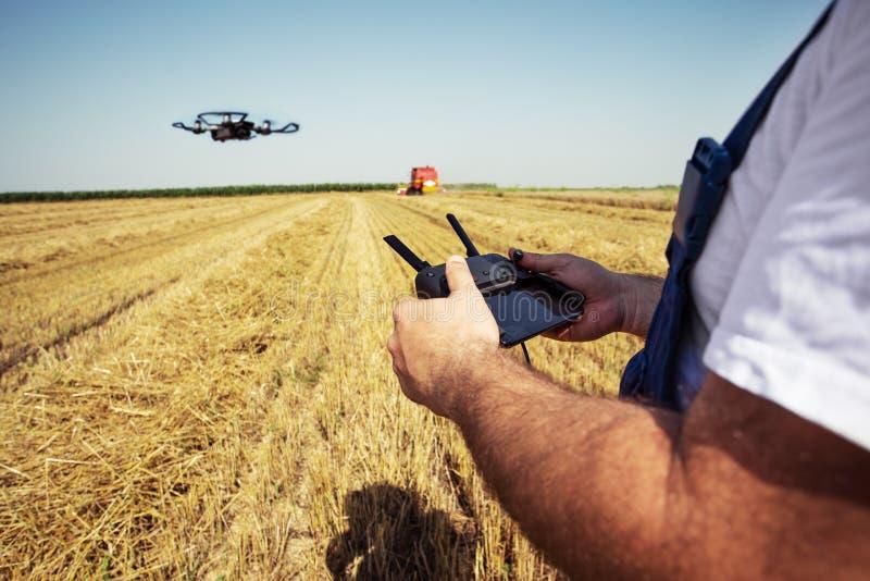 L'uomo tiene il regolatore a distanza con le sue mani mentre l'elicottero sta volando sul fondo Nuove tecnologie agricole e raggi fotografia stock libera da diritti