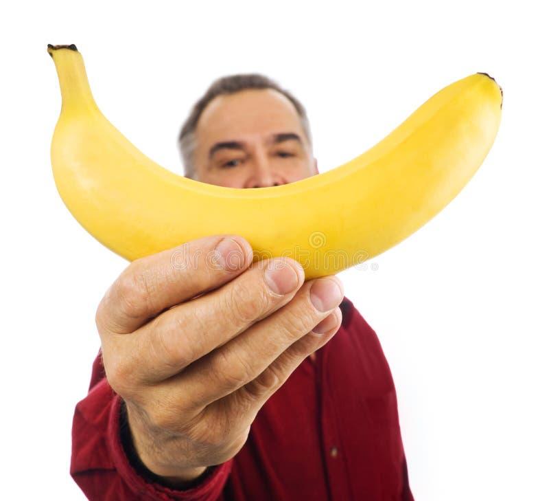 L'uomo tiene la banana davanti al suo fronte fotografia stock