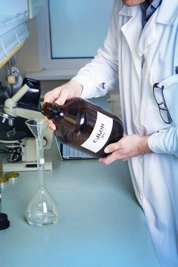 L'uomo tiene la bottiglia con la formula scritta dell'alcool fotografie stock libere da diritti