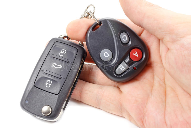 L'uomo tiene la chiave di accensione ed il telecomando disponibili della porta del garage immagini stock