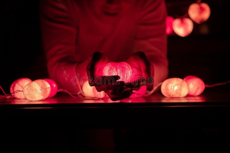 L'uomo tiene la lampada leggera principale di forma del cuore in sue mani nella stanza scura fotografia stock