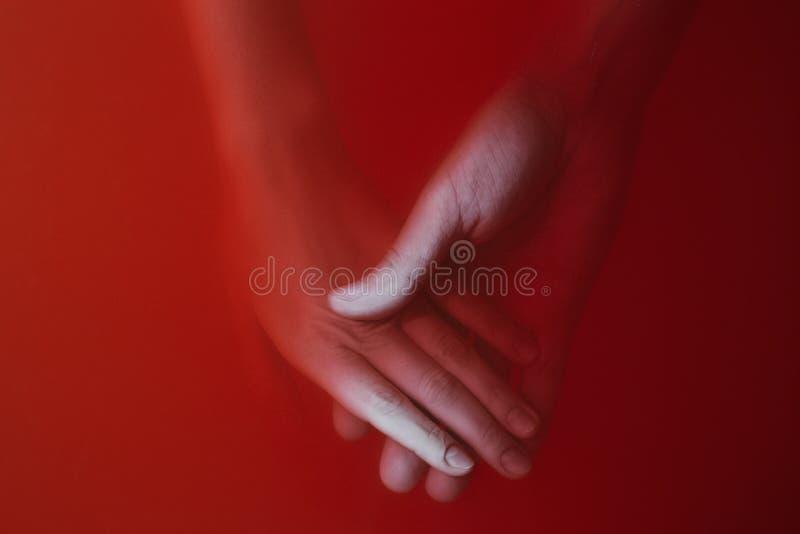 L'uomo tiene la mano della ragazza nell'acqua con le pitture rosse, nel concetto di amore, nella copertura di un giallo o in un g immagini stock libere da diritti