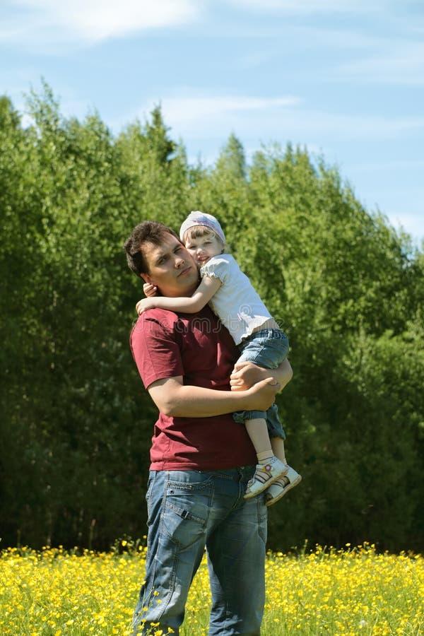 L'uomo tiene la piccola figlia fra i fiori gialli immagine stock
