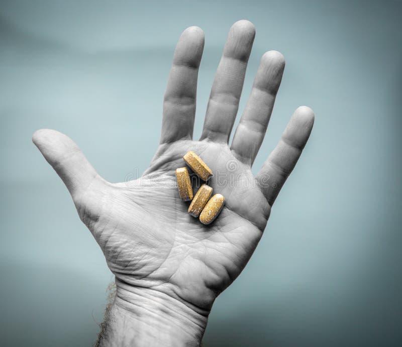L'uomo tiene le vitamine o le pillole di prescrizione in palma della mano Concetto di dipendenza o di sanit? immagine stock libera da diritti