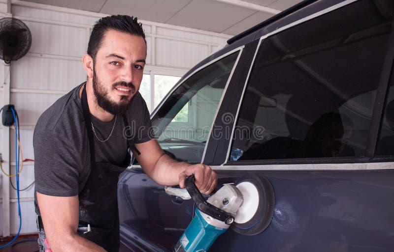 L'uomo tiene lo strumento di lucidatura dell'automobile nelle mani e nel sorriso fotografie stock