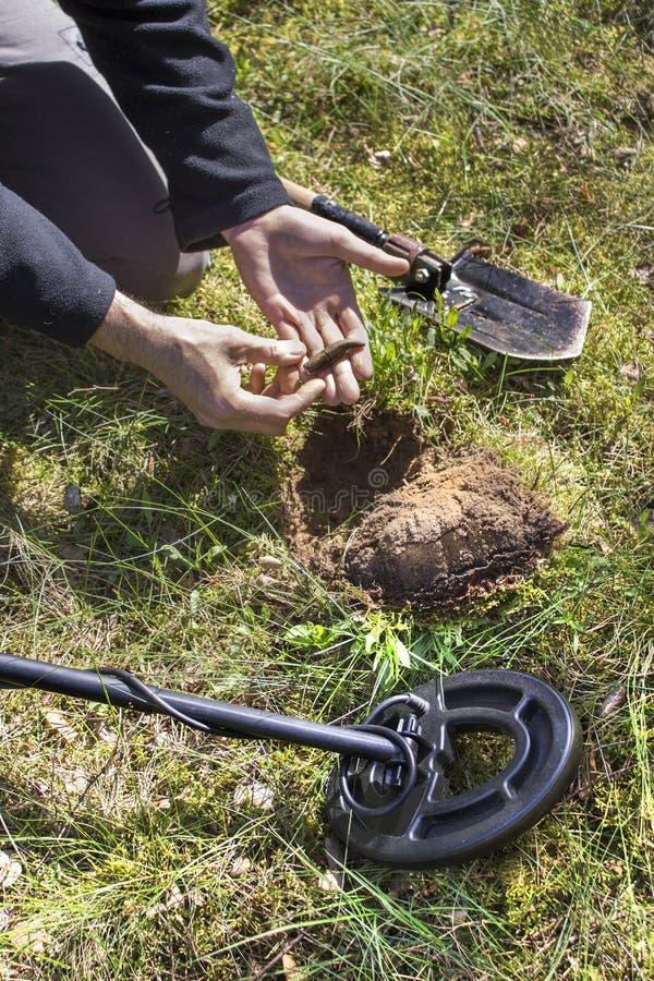L'uomo tiene in sua mano che un oggetto ha trovato nella terra Un metal detector e una pala si trovano accanto lui immagini stock