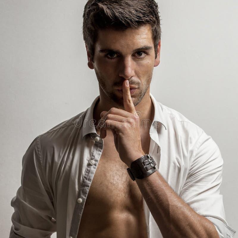 L'uomo tiene un dito sulle sue labbra con una camicia aperta fotografie stock libere da diritti