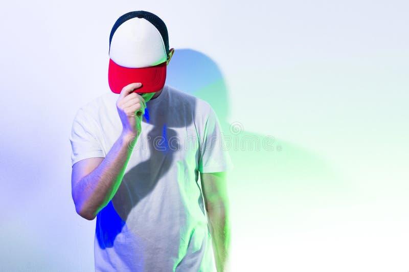 L'uomo, tipo nel berretto da baseball bianco e rosso in bianco, su una b bianca fotografia stock libera da diritti