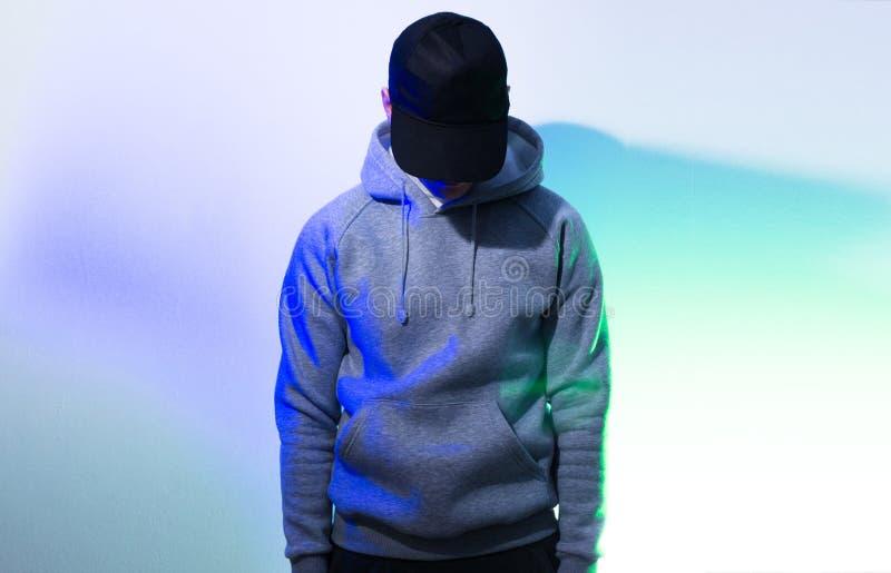 L'uomo, tipo nel nero in bianco, berretto da baseball, maglia con cappuccio grigia, sopra fotografia stock libera da diritti