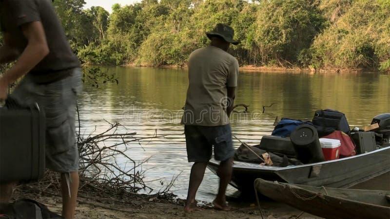 L'uomo trascina la barca sopra la riva del lago con i bagagli fotografia stock libera da diritti
