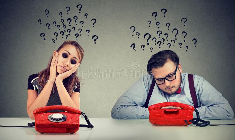 L'uomo triste e la donna che aspettano una telefonata l'uno dall'altro hanno molte domande immagini stock