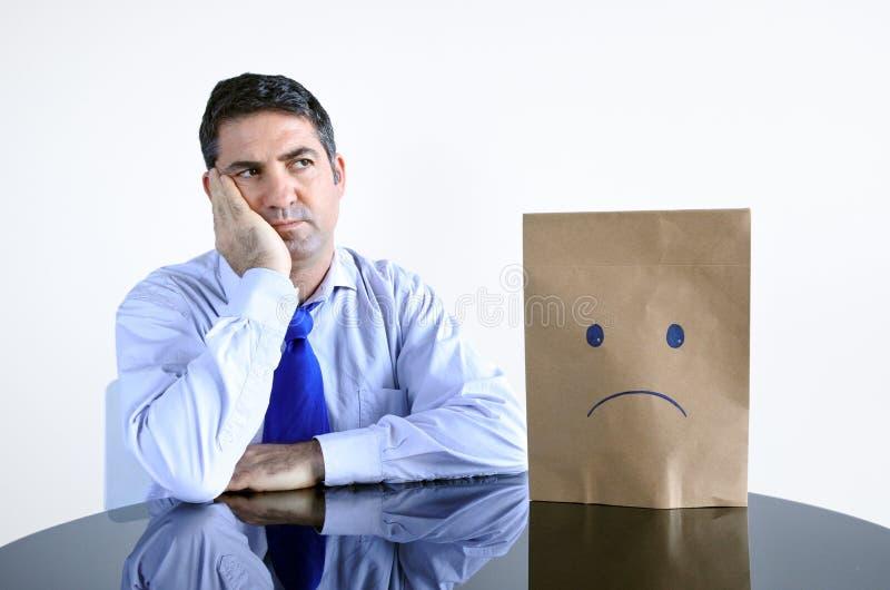 L'uomo triste si siede alla tavola da solo fotografie stock