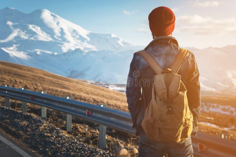 L'uomo turistico barbuto dei pantaloni a vita bassa in occhiali da sole con uno zaino sta indietro su un urto del bordo della str immagine stock