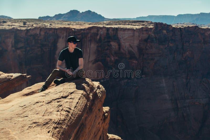 L'uomo turistico che si siede sulla roccia del bordo della scogliera della montagna e gode della vista dopo l'escursione al giorn fotografie stock