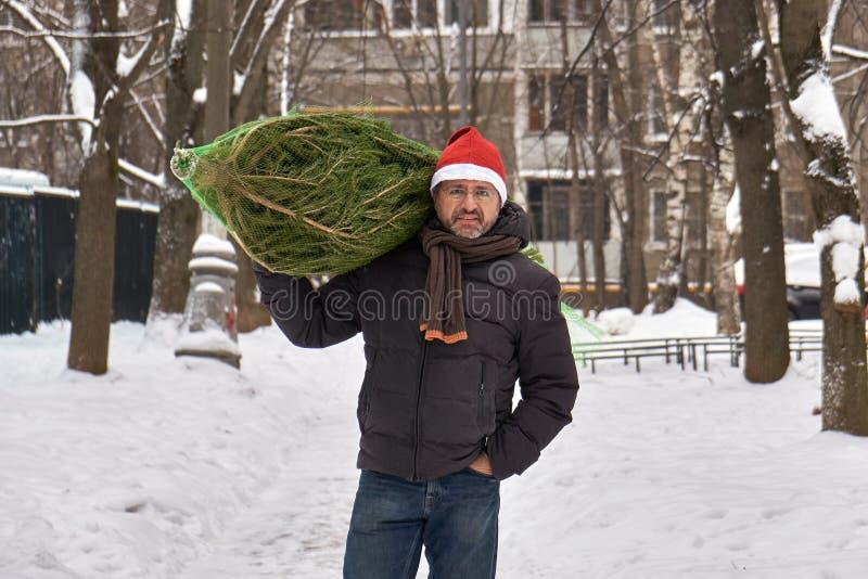 L'uomo in un cappello rosso di Santa continua la sua spalla un albero di Natale imballato in una griglia comprato appena al merca fotografia stock