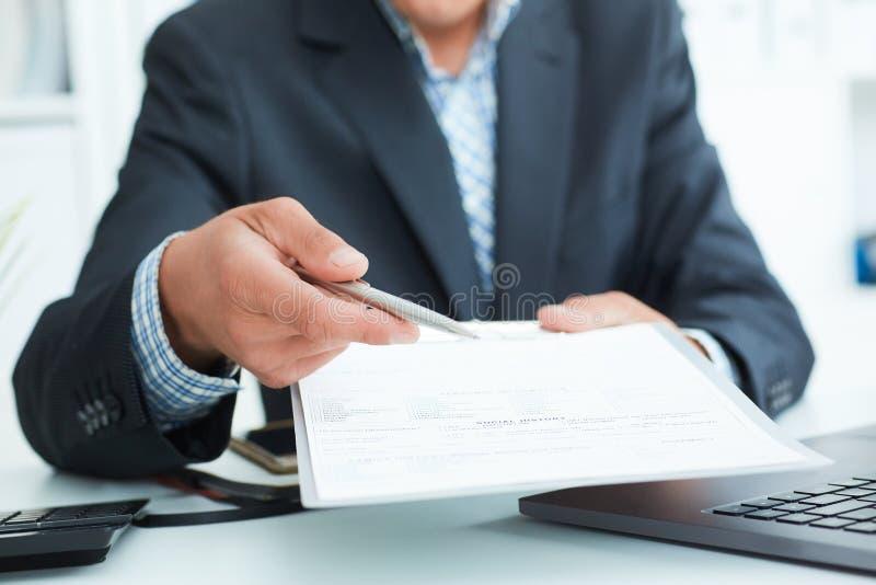 L'uomo in un vestito offre firmare un contratto che tiene una penna ed i documenti per la firma immagine stock