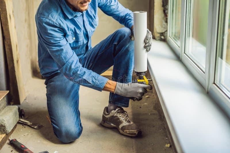 L'uomo in una camicia blu fa l'installazione della finestra Facendo uso di una schiuma del montaggio immagini stock libere da diritti