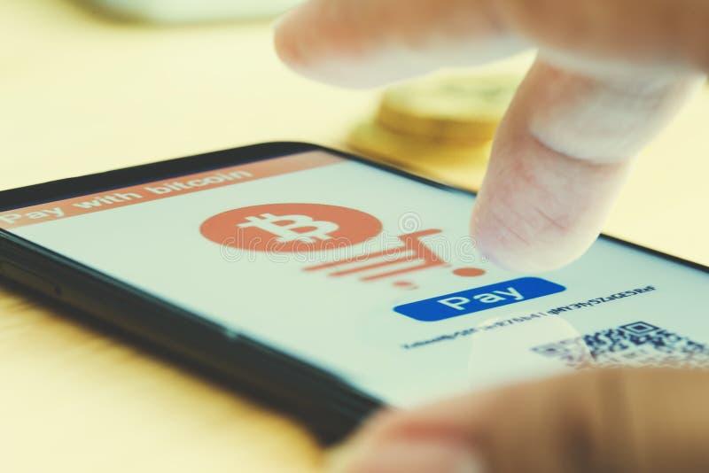 L'uomo usa la paga dello Smart Phone con bitcoin immagini stock