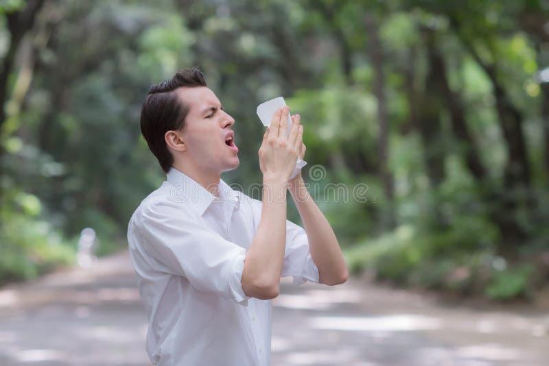 L'uomo usa lo starnuto della carta velina dovuto avere allergia del polline fotografie stock
