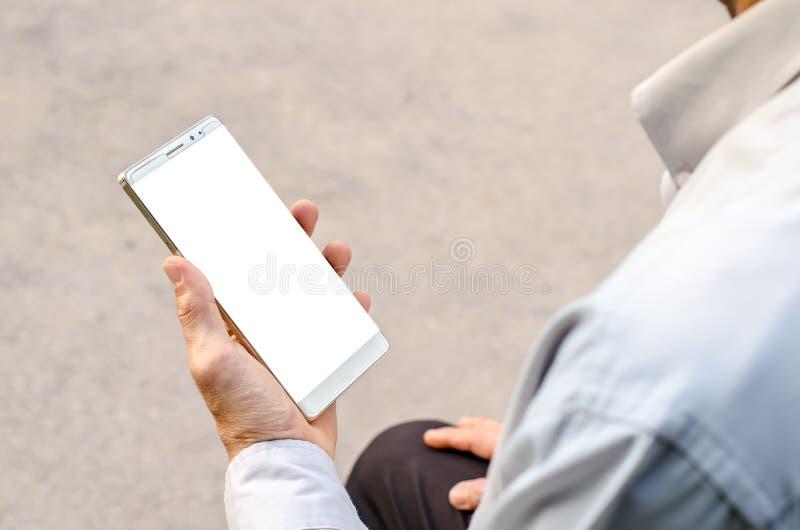 L'uomo utilizza il suo telefono cellulare è parco all'aperto fotografia stock libera da diritti