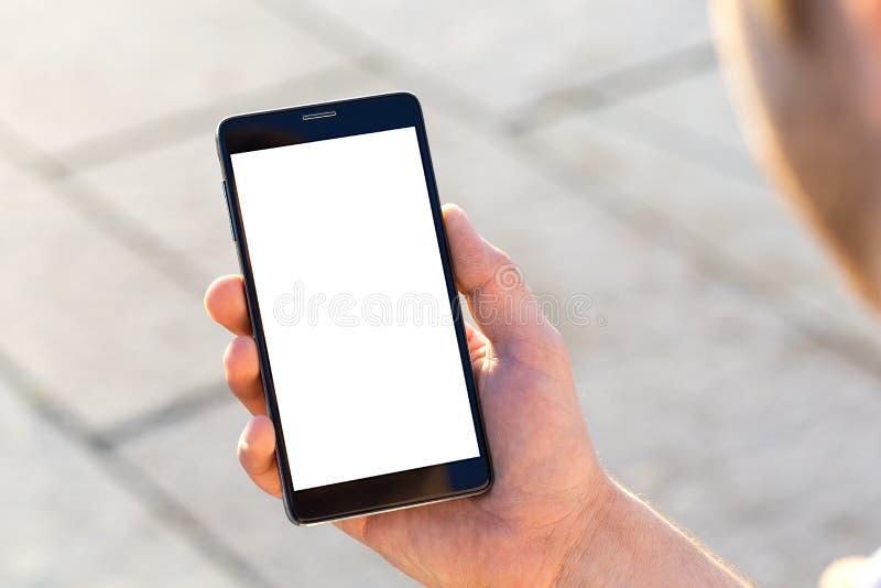 L'uomo utilizza il suo telefono cellulare all'aperto fotografia stock