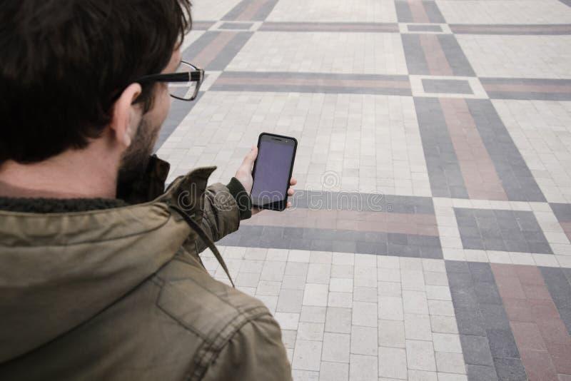 L'uomo utilizza il suo telefono cellulare all'aperto, alto vicino fotografia stock