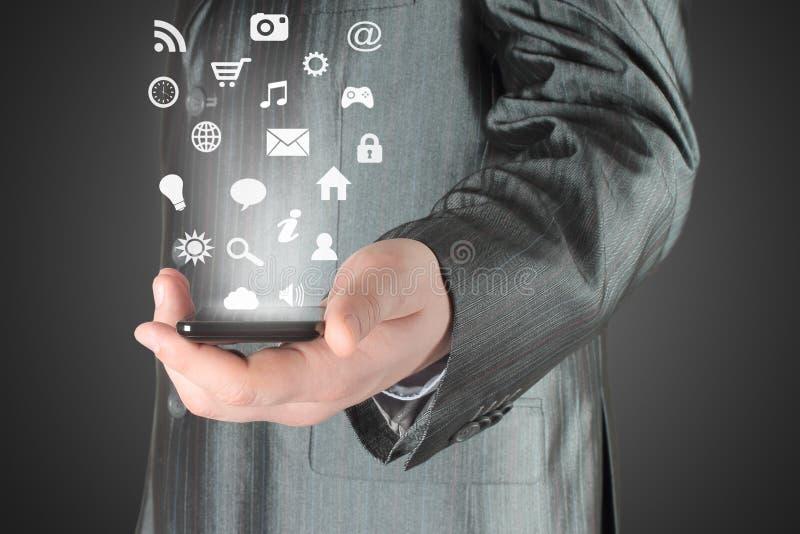 L'uomo utilizza lo Smart Phone con le icone fotografia stock libera da diritti