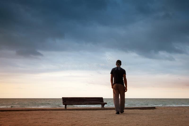 L'uomo va al mare vicino al vecchio banco vuoto di legno fotografia stock
