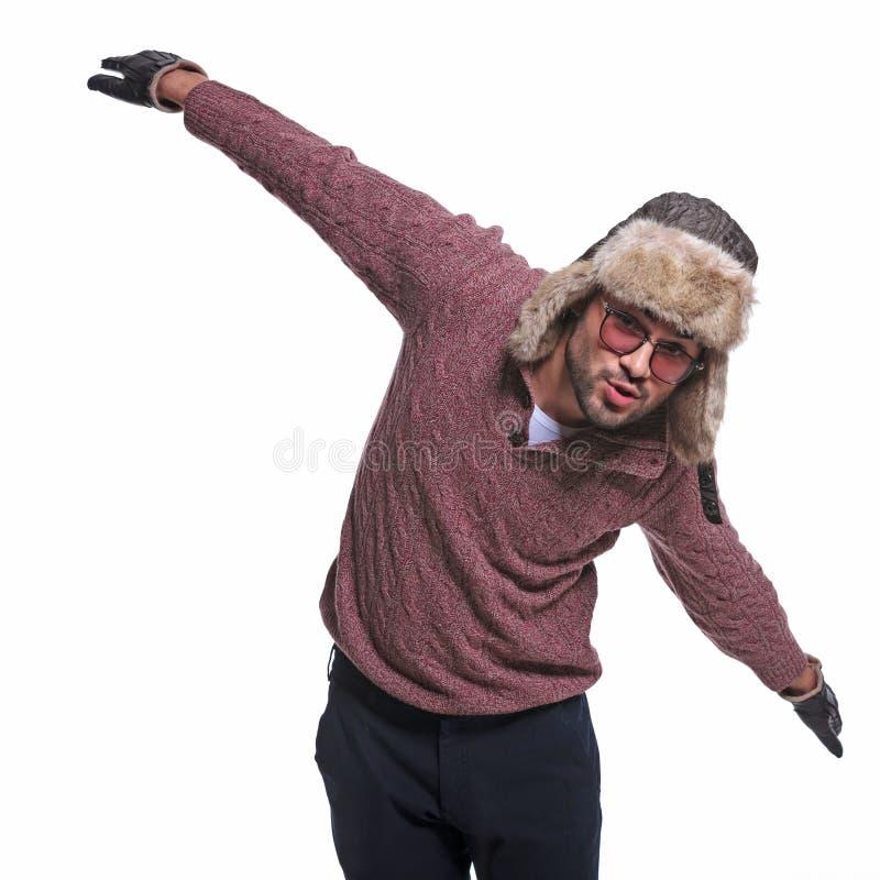 L'uomo in vestiti dell'inverno sta impersonando un aeroplano fotografia stock libera da diritti