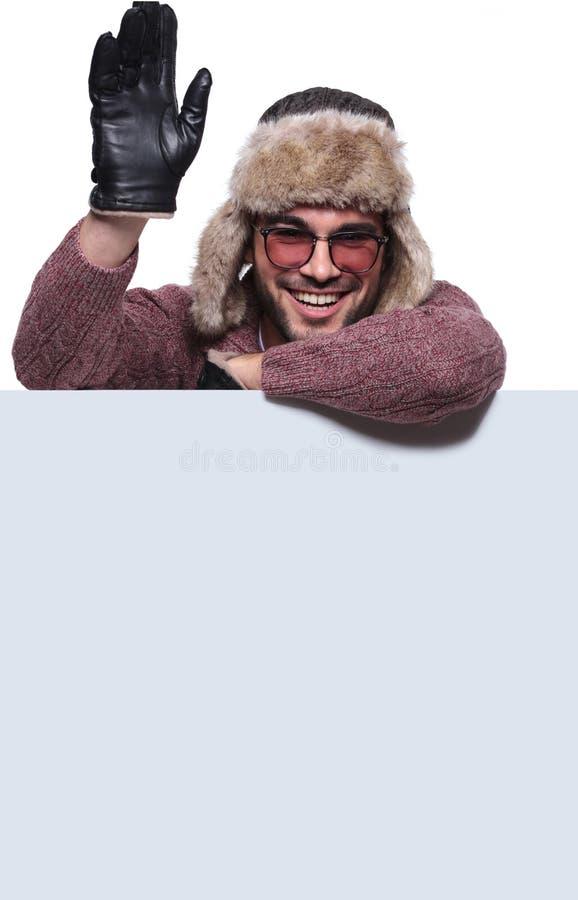 L'uomo in vestiti dell'inverno vi accoglie mentre presenta il bordo fotografie stock libere da diritti