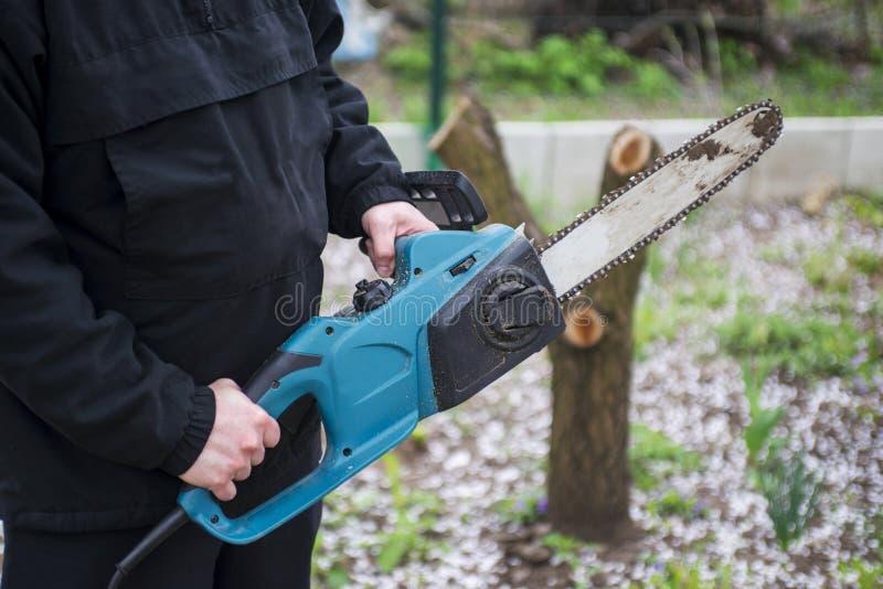 L'uomo in vestiti neri tiene la motosega blu con le sue mani pulite immagine stock libera da diritti