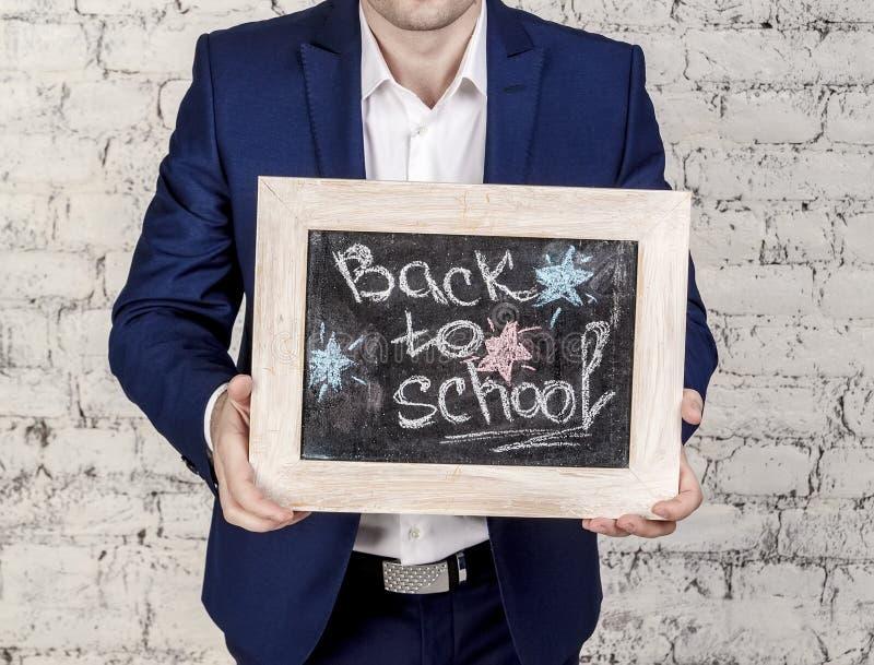 L'uomo in vestito classico tiene la lavagna con il titolo di nuovo alla scuola sopra il fondo bianco dei mattoni Nessun fronte, i immagini stock