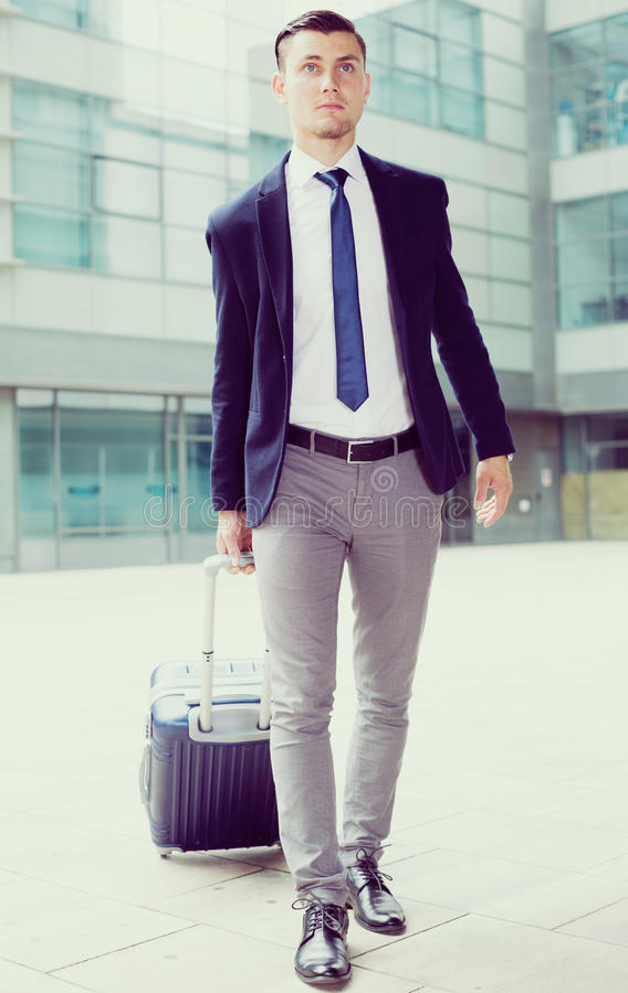 L'uomo in vestito con la valigia sta restando fotografie stock libere da diritti