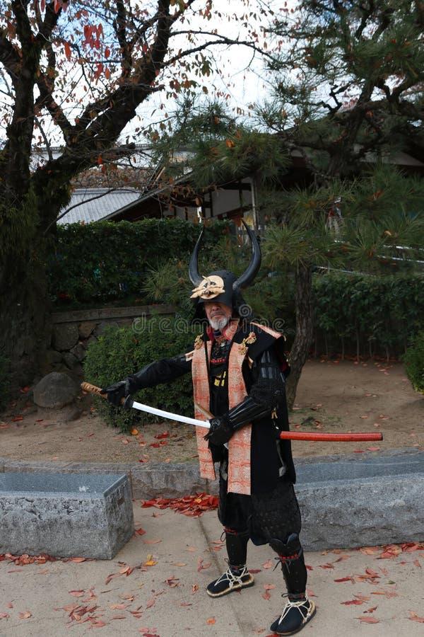 L'uomo in vestito dal samurai, turista può essere prende una foto per tenere un memoriale al castello di Himeji immagini stock