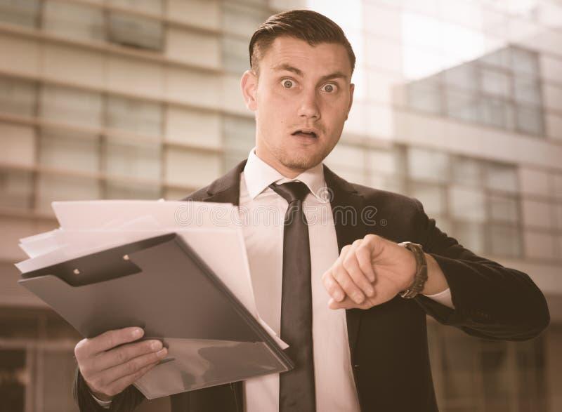 L'uomo in vestito sta considerando l'orologio vicino all'ufficio immagini stock