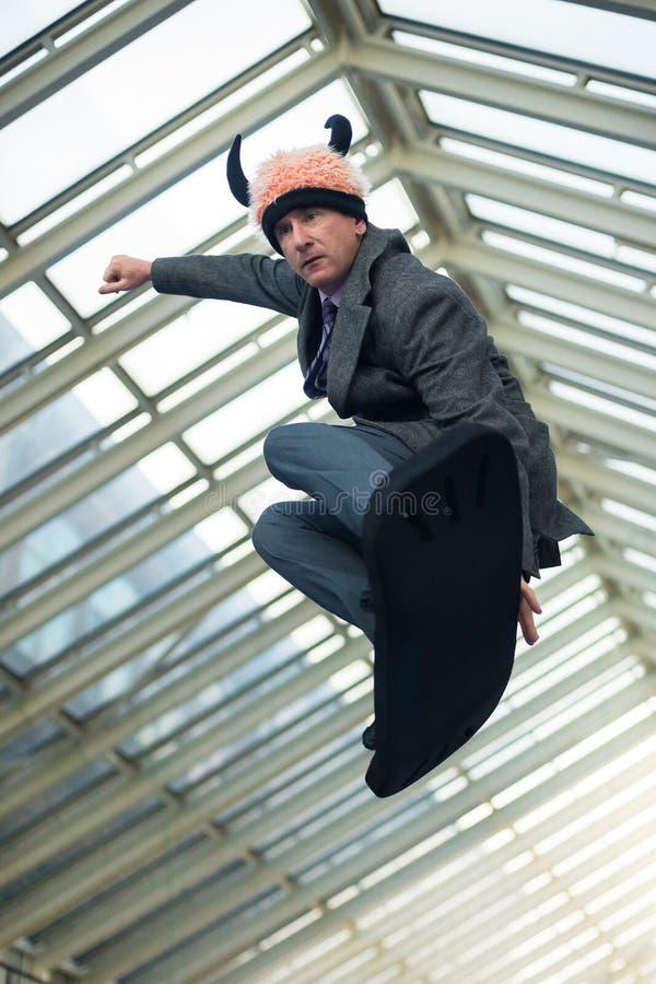 L'uomo, vestito in un vestito ed in un cappello divertente, salta fotografie stock libere da diritti