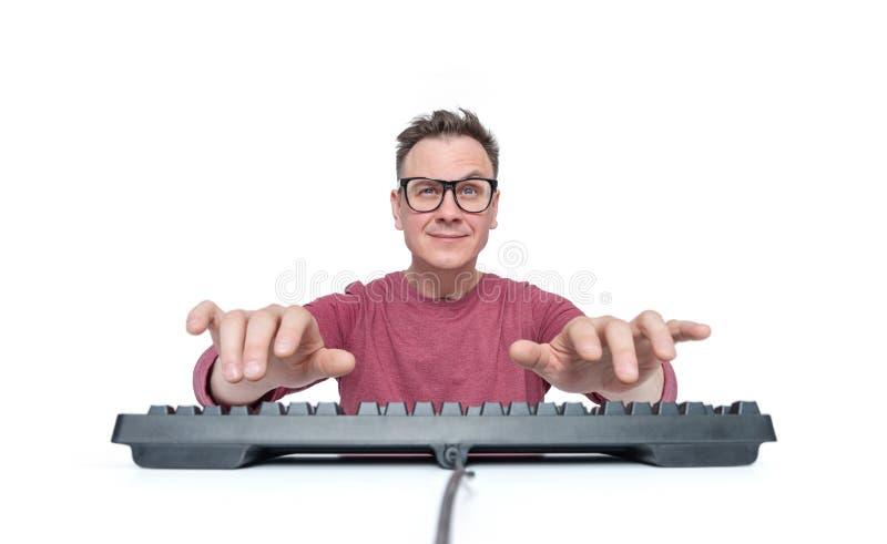 L'uomo in vetri ed in una maglietta rossa sta scrivendo sulla tastiera, per esaminare la macchina fotografica, isolata su fondo b fotografia stock