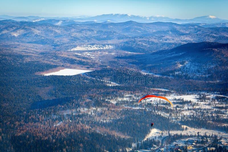 L'uomo vola con un paracadute arancio fotografia stock