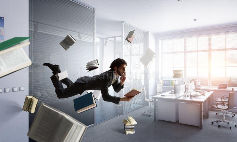 L'uomo vola e lavora al computer portatile Media misti immagine stock libera da diritti